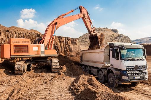 Construction Vehicle「Excavator loading dumper trucks at sunset」:スマホ壁紙(8)
