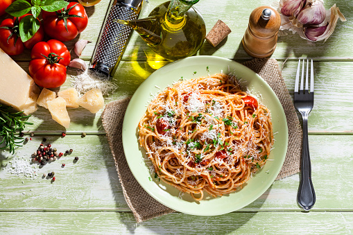 Garlic Clove「Pasta plate and ingredients on green kitchen table」:スマホ壁紙(18)