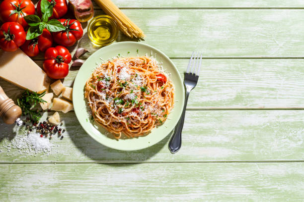 Pasta plate and ingredients on green kitchen table:スマホ壁紙(壁紙.com)