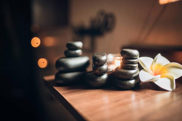 Lit candles and black massage stones in Zen spa:スマホ壁紙(壁紙.com)