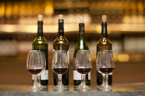 Tasting「Red wine glasses and wine bottles on a counter of a wine cellar」:スマホ壁紙(15)