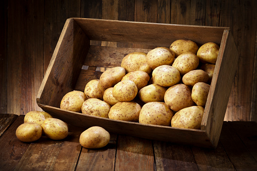 Tilt「Raw potatoes in a crate on rustic wood table」:スマホ壁紙(3)