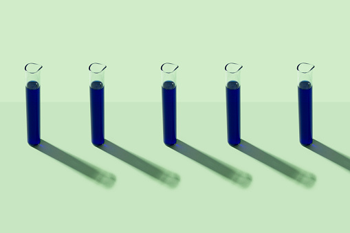 Chemical「Row of test tubes with blue liquid, green background」:スマホ壁紙(3)