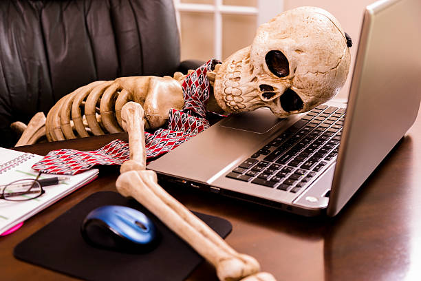 Working to death.  Business man's skeleton using laptop in office.:スマホ壁紙(壁紙.com)