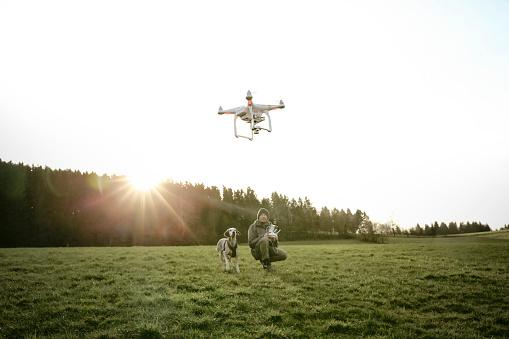 白人「Man on a meadow flying drone while his dog watching」:スマホ壁紙(5)