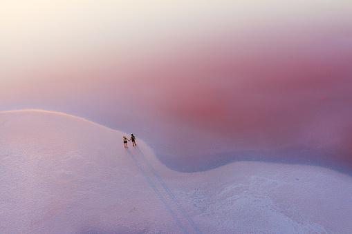 白人「ピンクの塩湖を歩く異性愛者の風光明媚な空中写真」:スマホ壁紙(4)