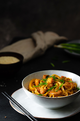 Asian Food「Udon stir-fry noodles with shrimp and vegetables on black background in dark and moody style」:スマホ壁紙(12)