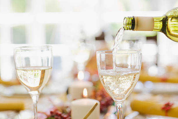 White wine being poured into glass on table:スマホ壁紙(壁紙.com)