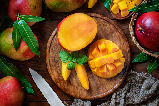 Halved「Tropical Fruits: Sliced mangos in a wooden plate on a table in rustic kitchen」:スマホ壁紙(12)