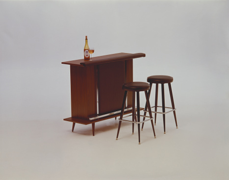Bar Counter「Beer bottle and glasses on wooden table beside wooden stools」:スマホ壁紙(11)