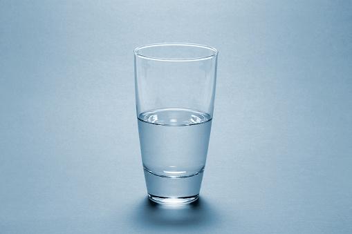 Full「Half full water glass over blue background」:スマホ壁紙(0)