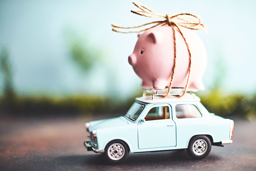 Insurance「Little pink piggy bank tied to the top of an old car」:スマホ壁紙(0)