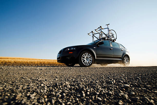 A black car with two road bikes on top cruises along a dirt road leaving a trail of dust in the dist:スマホ壁紙(壁紙.com)