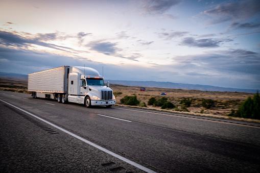 Trucking「Long Haul Semi Trucks Speeding Down a Four Lane Highway To Delivery Their Loads」:スマホ壁紙(15)