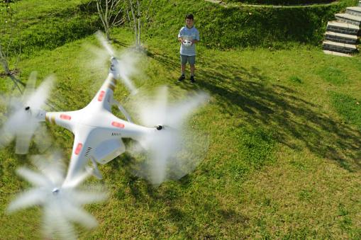 無人操縦機「Boy playing with drone in garden」:スマホ壁紙(18)