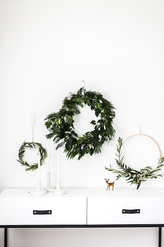 Christmas Decoration「Wreaths hanging on a wall by a sideboard」:スマホ壁紙(5)