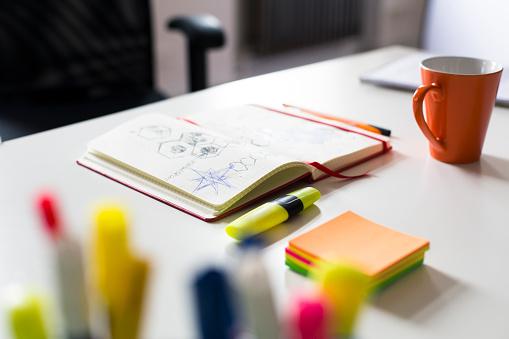 クローズアップ「Notebook with sketch, highlighters and cup of coffee on desk in office」:スマホ壁紙(13)