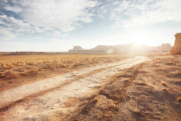 Dirt road in arid desert landscape with distant cliffs and sunlight:スマホ壁紙(壁紙.com)