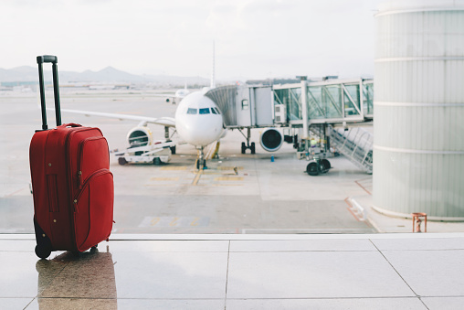 Travel「Red suitcase at airport, airplane in background」:スマホ壁紙(1)