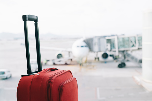 Travel「Red suitcase at airport, airplane in background」:スマホ壁紙(4)