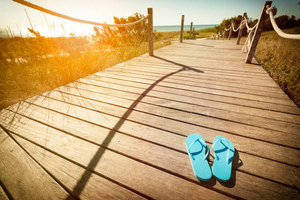 Flip flops on a wooden footpath to the beach on the dunes at sunset:スマホ壁紙(壁紙.com)