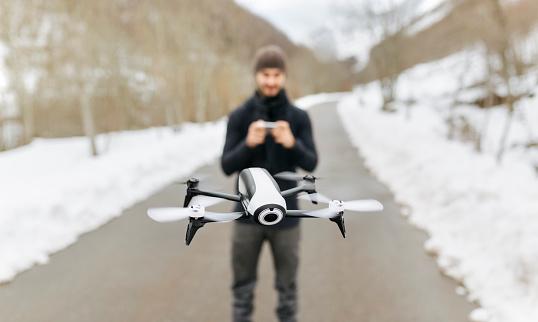 1人「Spain, Asturias, man navigating a drone in the snowy mountains」:スマホ壁紙(13)